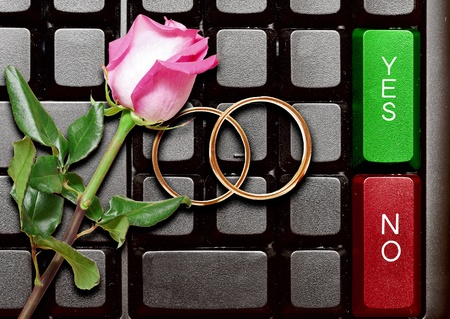incertitude: Wedding rings and red roses on computer keyboard. answer from a marry proposal