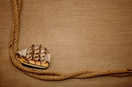 rope and model classic boat on canvas of burlap photo