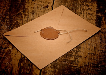 seal wax: sealed brown envelope on wood background