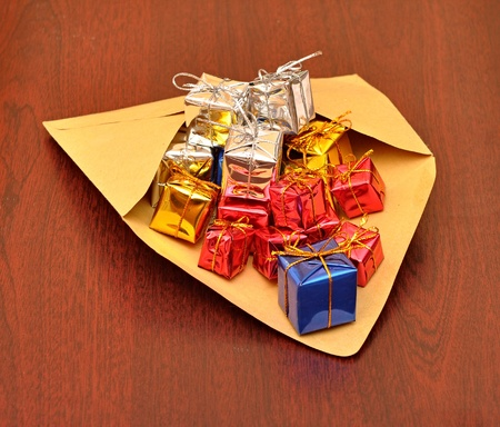 colorful gift boxes with envelope on wood background photo