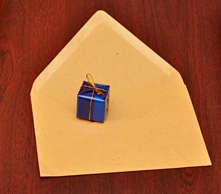 gift box with envelope on wood background photo