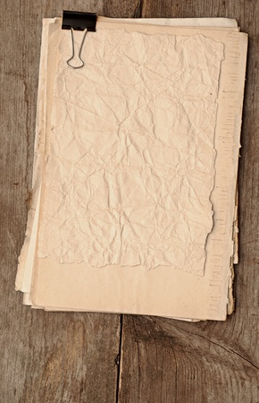 old paper sheets with clip on wooden background Stock Photo - 11589468