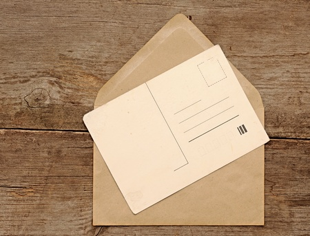 Blank vintage postcard and envelope on old wooden background photo