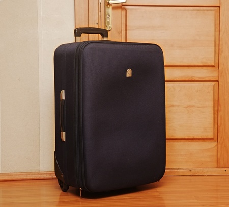 return trip: One black suitcase sitting on the entrance inside the front door of a home