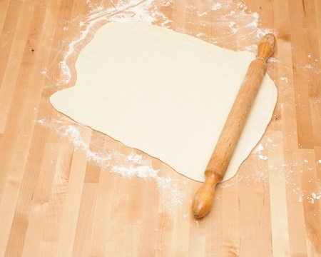 flatten: Classic wooden rolling pin with freshly prepared dough and dusting of flour.
