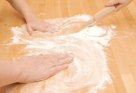 A child is helping mom to knead the dough for baking  photo