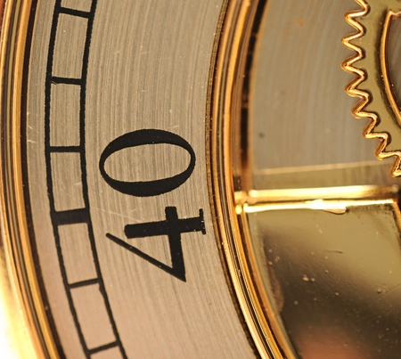 closeup golden clock with gears on white photo