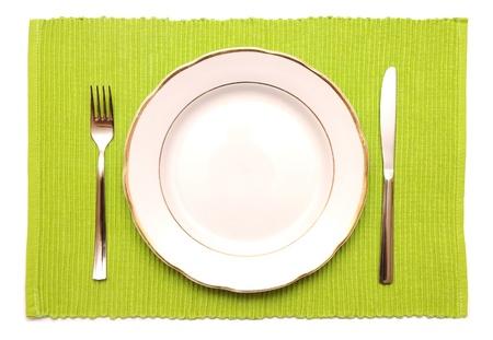 Het mes, vork en witte plaat op een groene servet op een witte achtergrond Stockfoto