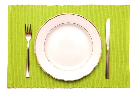 The knife, fork and white plate on a green napkin on a white background photo