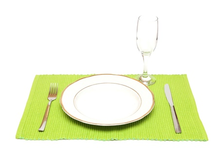 A dinner plate, knife, fork  and wine glass on a green napkin  photo