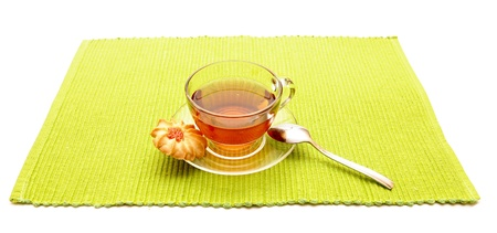 the cup of tea with spoon on the green napkin photo