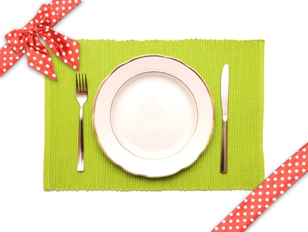 The knife, fork and white plate on a green napkin with dotted red satin gift bow and ribbon on a white background photo
