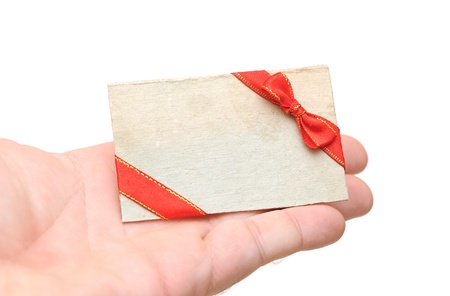blank gift tag with red ribbon and bow in hand holding on white photo