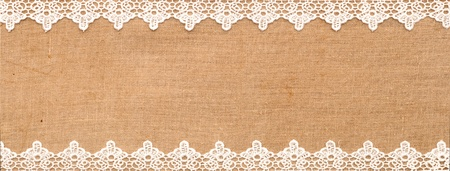 sewn up: White lace on the canvas background Stock Photo