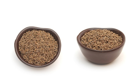 spices cumin seeds in a clay bowl isolated on a white background photo