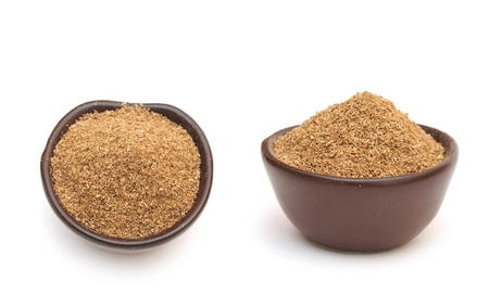 coriander powder in a clay bowl isolated on a white background photo