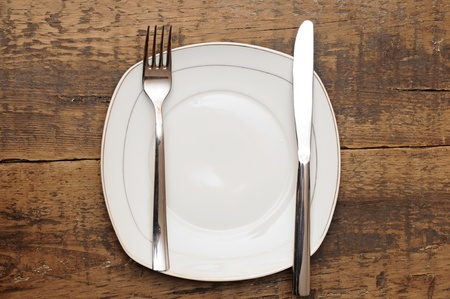 Empty dish knife and fork on wood table photo