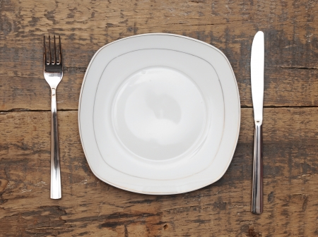 Empty dish knife and fork on grungy wood table