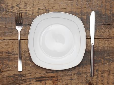 Lege schaal mes en vork op grungy houten tafel Stockfoto