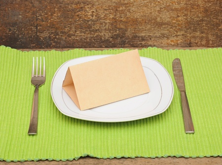 Empty dish with old paper, knife and fork and green napkin on wood table photo
