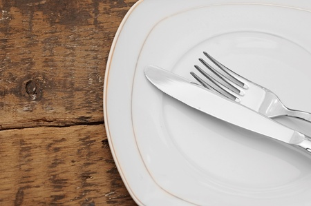 White empty plate with fork and knife on wood table