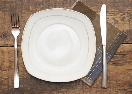 plate setting: Empty dish, knife and fork and brown napkin on wood table  Stock Photo