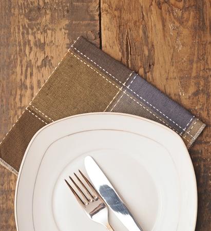 cubiertos de plata: primer plano blanco vac�o plato con servilleta de color marr�n cuchillo y el tenedor en la mesa de madera Foto de archivo