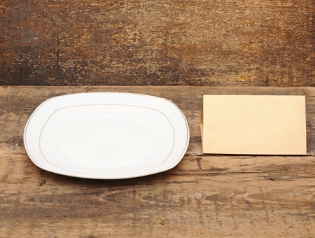 White empty plate with fork and knife on wood table Stock Photo - 12893051