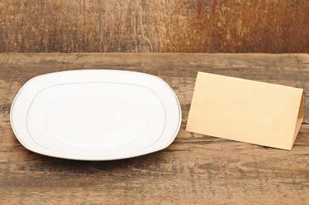 White empty plate with old paper on wood table photo