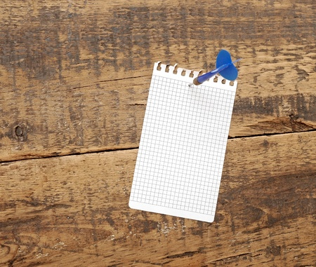 dart in blank notepad on a vintage wooden board Stock Photo - 13211217