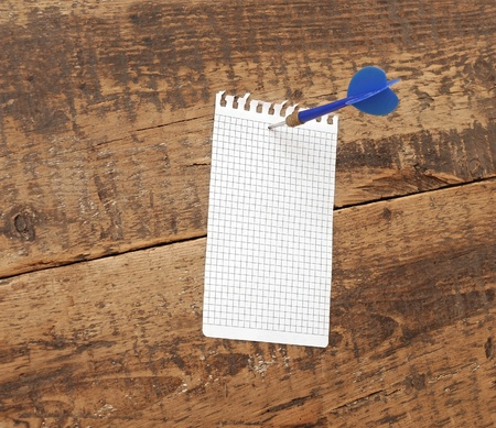 dart in blank notepad on a vintage wooden board  Stock Photo - 13211119
