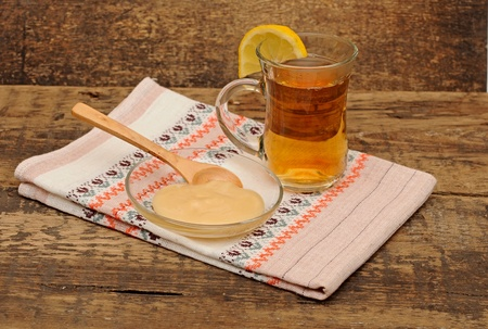 glass cup of tea with honey on colorful napkin photo
