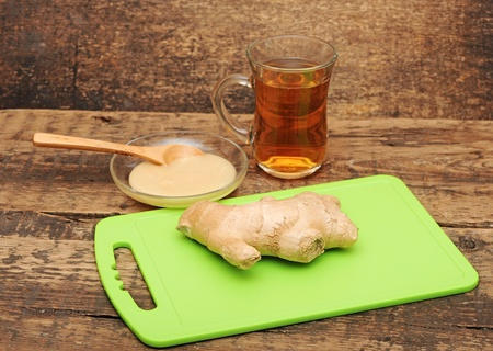 Healthy ginger tea on wooden background photo