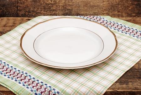single white plate on old wood background photo