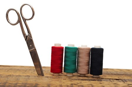 tools for needlework colorful threads and scissors on wooden background photo