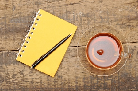 notebooks, pens, tea on the table photo