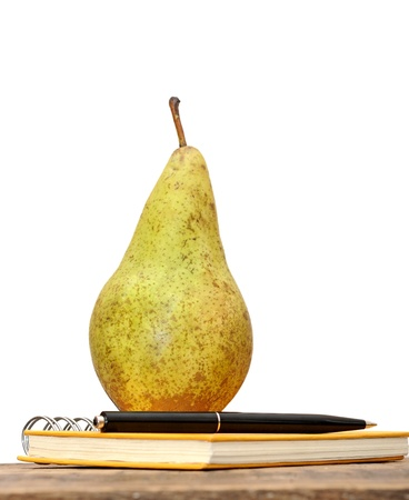 Pear and notebook on wood background Stock Photo - 13210381