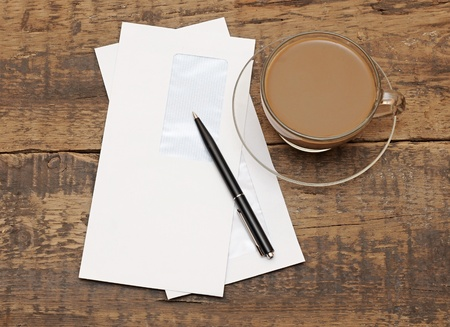 two white envelopes with black pen on wood background photo
