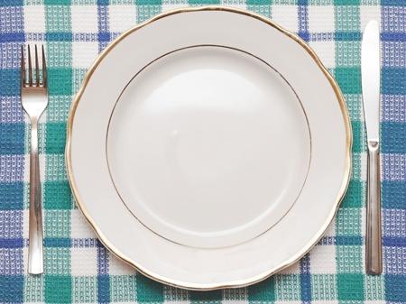 Mes, witte plaat en vork op blauw geruit tafelkleed