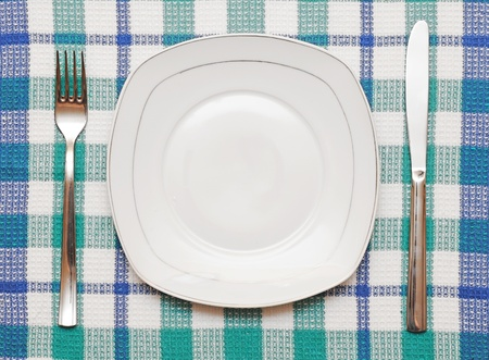 White empty plate with fork and knife on checkered tablecloth photo