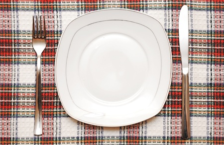 White empty plate with fork and knife on checkered tablecloth Stock Photo - 13211761