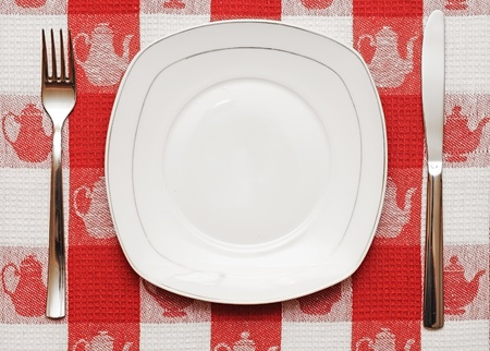 Knife, white plate and fork on red tablecloth photo