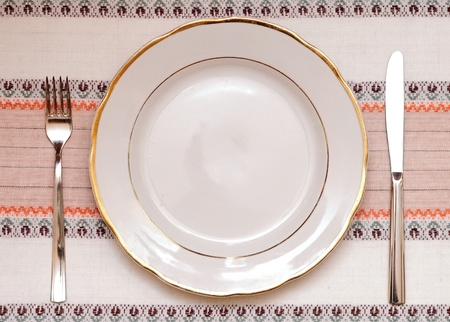 Knife, white plate and fork on tablecloth photo