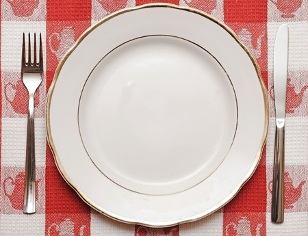 Knife, plate and fork on red tablecloth  photo