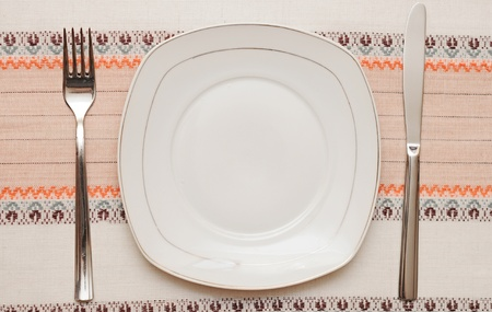Knife, white plate and fork on tablecloth Stock Photo - 13211856