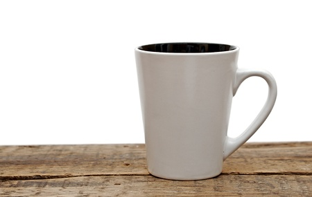 White mug empty blank for coffee  on a wooden table over white background photo