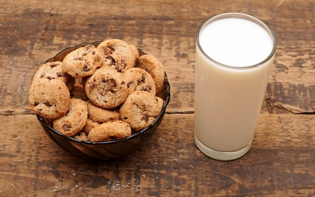 Glass of milk and chocolate chip cookies in a cup on wooden table photo