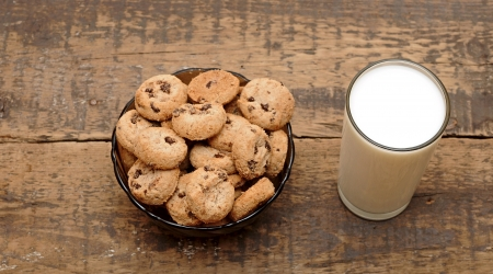 glass of milk and cookies on wooden table photo