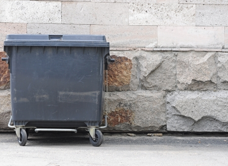 one plastic garbage can with wheels and folding lids. Near ragged wall.  photo