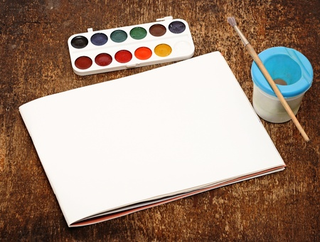 Set of art paints and brushes to paint and paper on wooden table photo